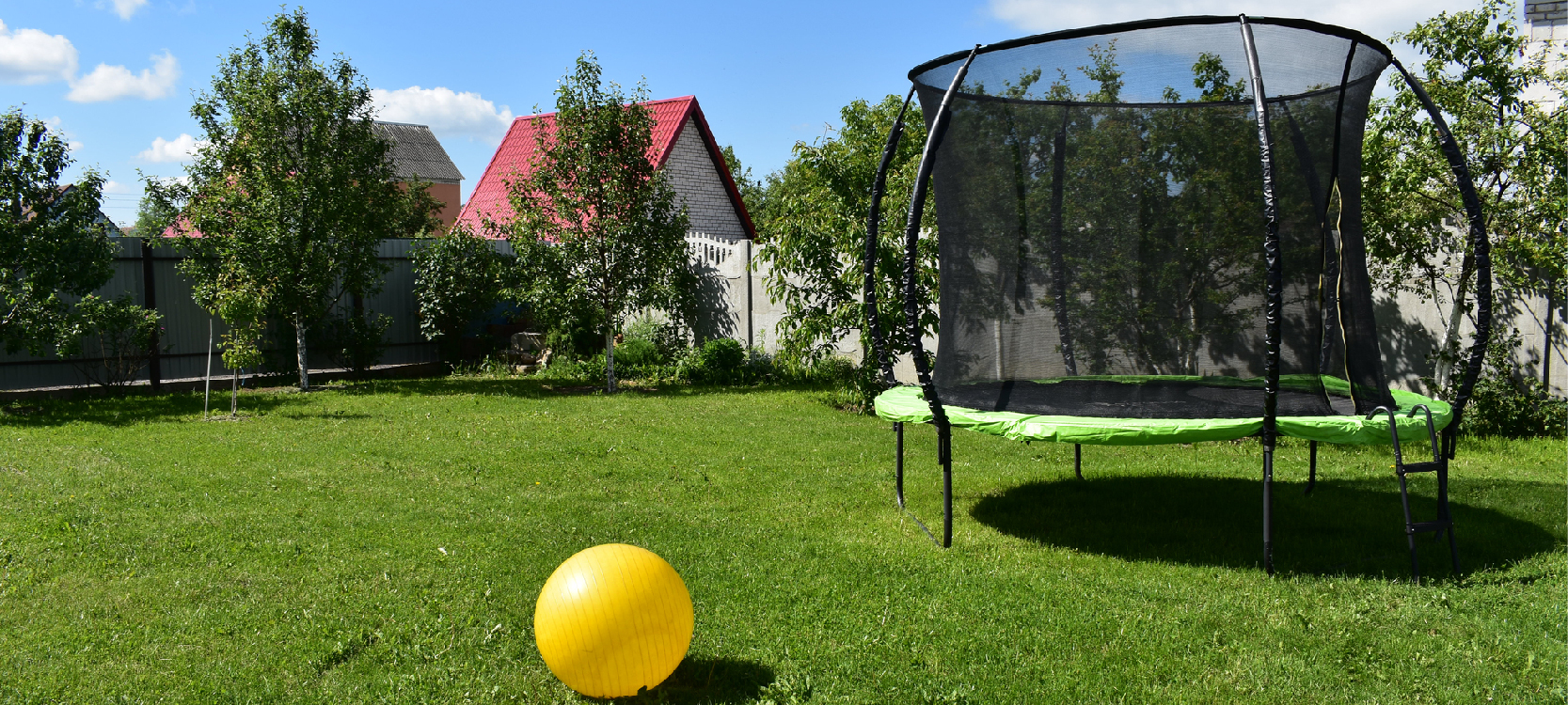 a trampoline with a ball in the warm outdoor backyard