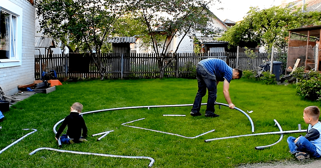 daddy and children building up a trampoline in the yard