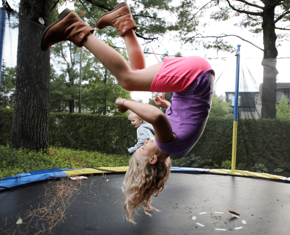 little girl doing a nicely back handsrping on trampoline