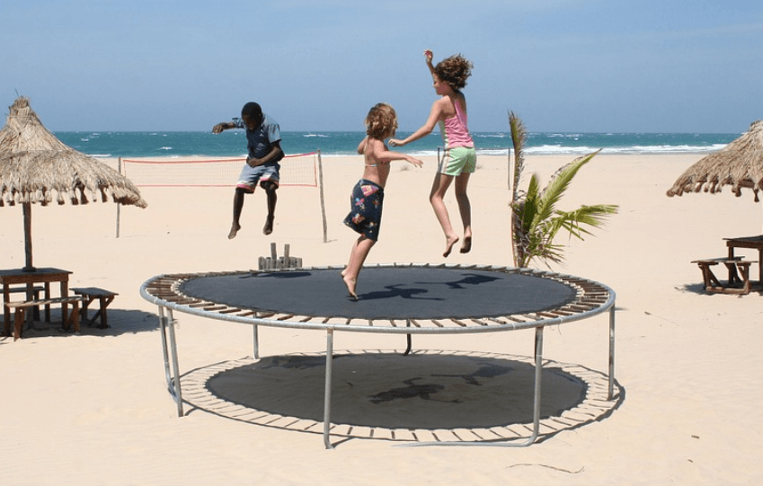 children playing with trampoline on the beach