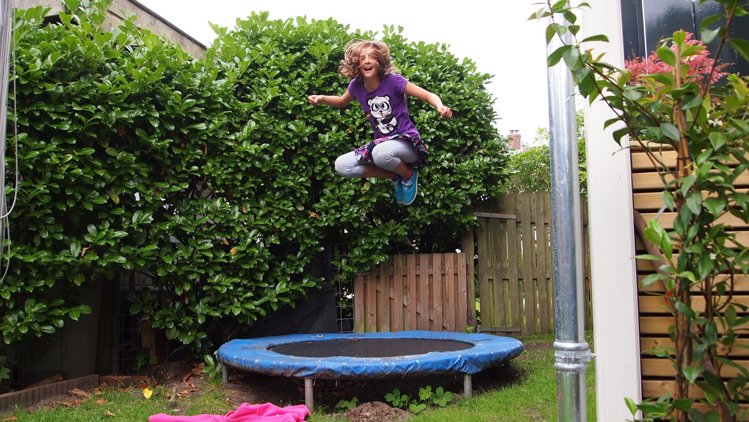 a girl bouncing happily in garden