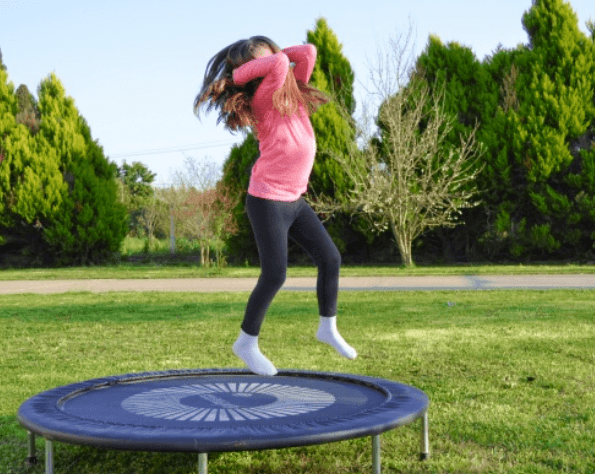 a little girl dancing nicely on single round trampoline