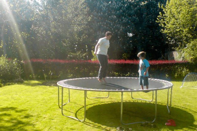 mama playing with son on round trampoline in sunny day