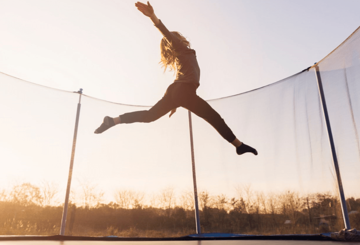 a girl jumping high on trampoline