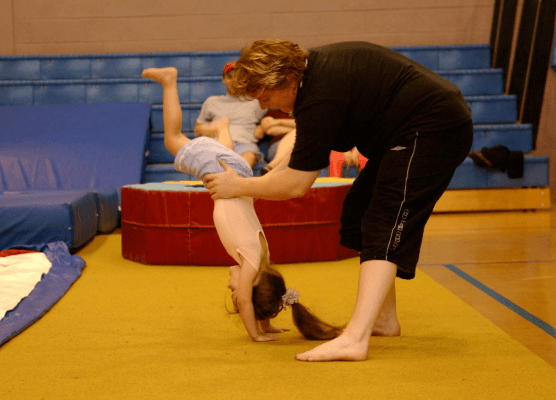 instructor teaching a baby girl to move back handspring safely