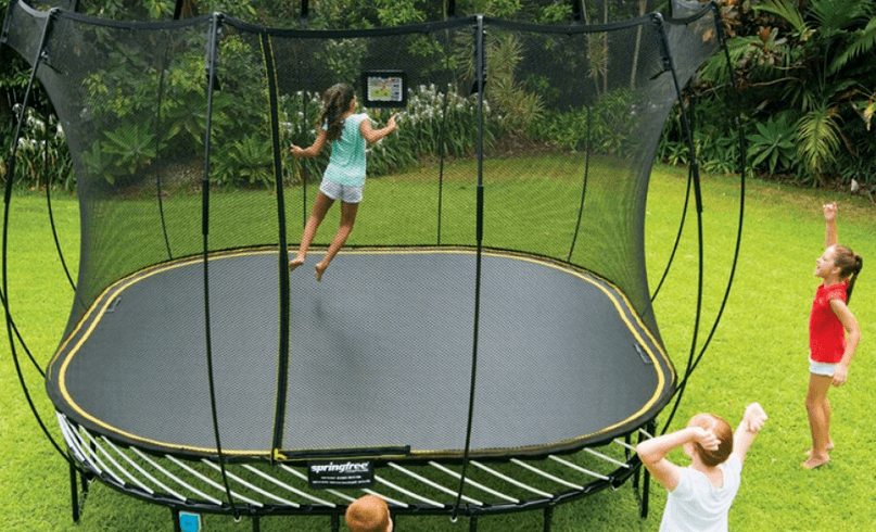 children playing with ova trampoline in the backyard